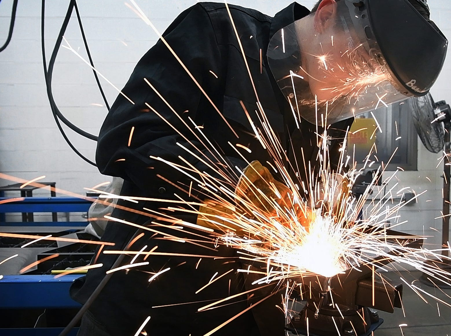 Sparks fly as Welding Technology student Jack Cantrell grinds welds on the steel base of a helicopter sculpture he's creating in honor of his late brother, Stephen Cantrell, who flew Blackhawk helicopters in Iraq and Afghanistan.