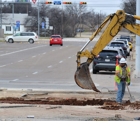 Traffic passes by as construction workers work to remove concrete from the Broad at 6th Street intersection Thursday morning.