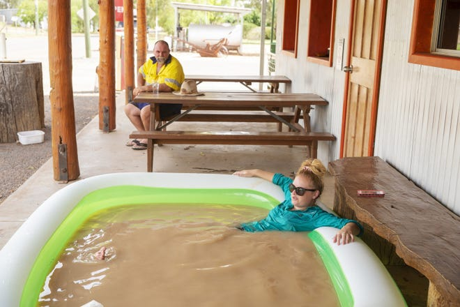 Jasmin Kew seeks relief from the heat in a blow up pool full of muddy water from the Darling River in 2019. The area is a bellwether for water-scarce regions.