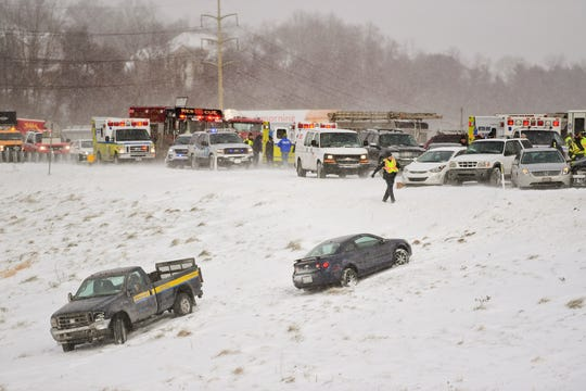 Emergency responders help victims from their cars after a multi-car pile up after a snow squall in Wyomissing, Pa., on Wednesday.