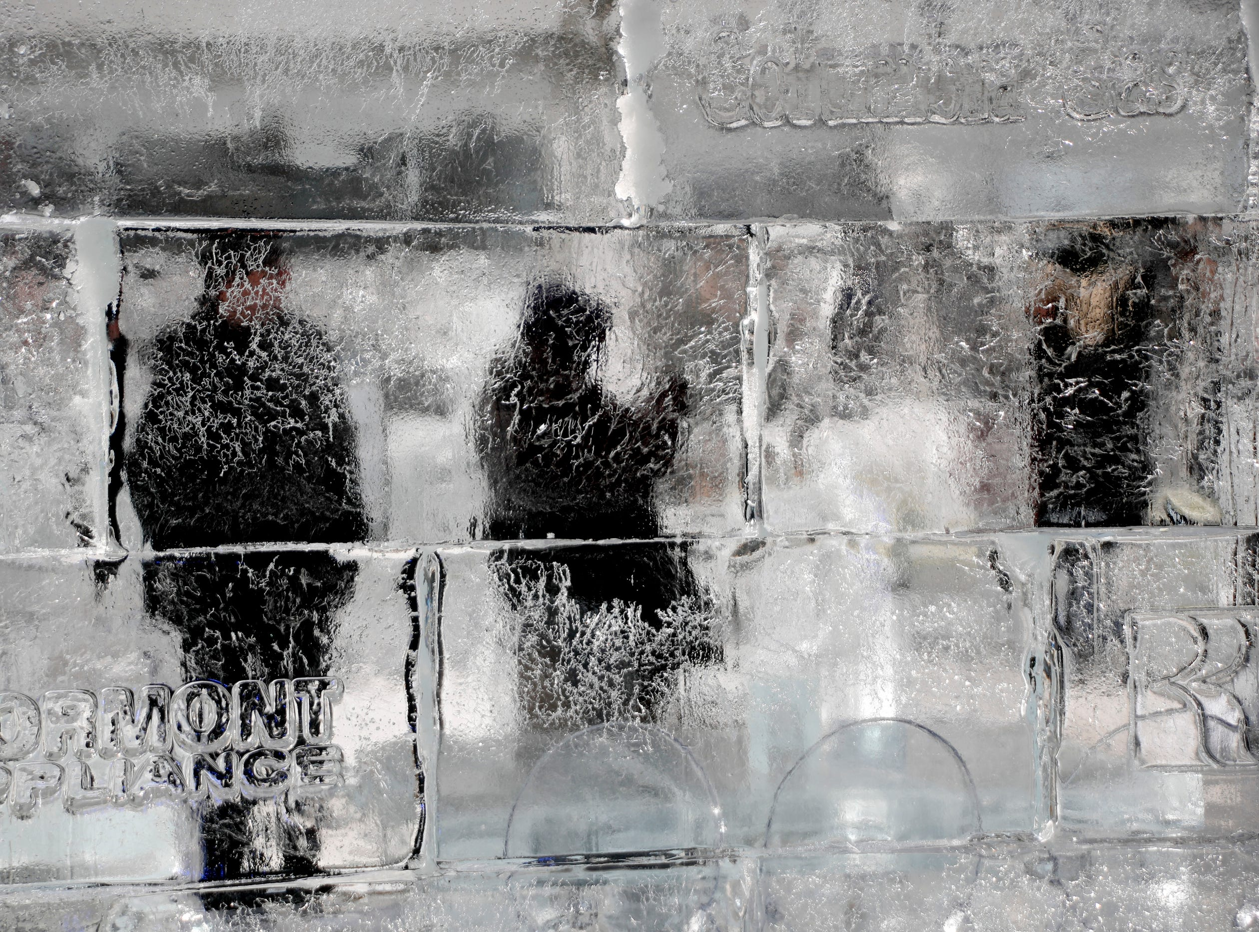 People visiting the ice house for the fifth annual Dollar Energy Fund Cool Down for Warmth event are visible through ice blocks on Friday, Jan. 25, 2019, in Pittsburgh. The program promotes awareness for families who go without heat in winter months, trying to raise money for utility assistance grants.