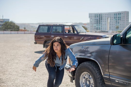 "Gloria (Gina Rodriguez) tries to stay alive in the middle of a firefight in ""Miss Bala."""