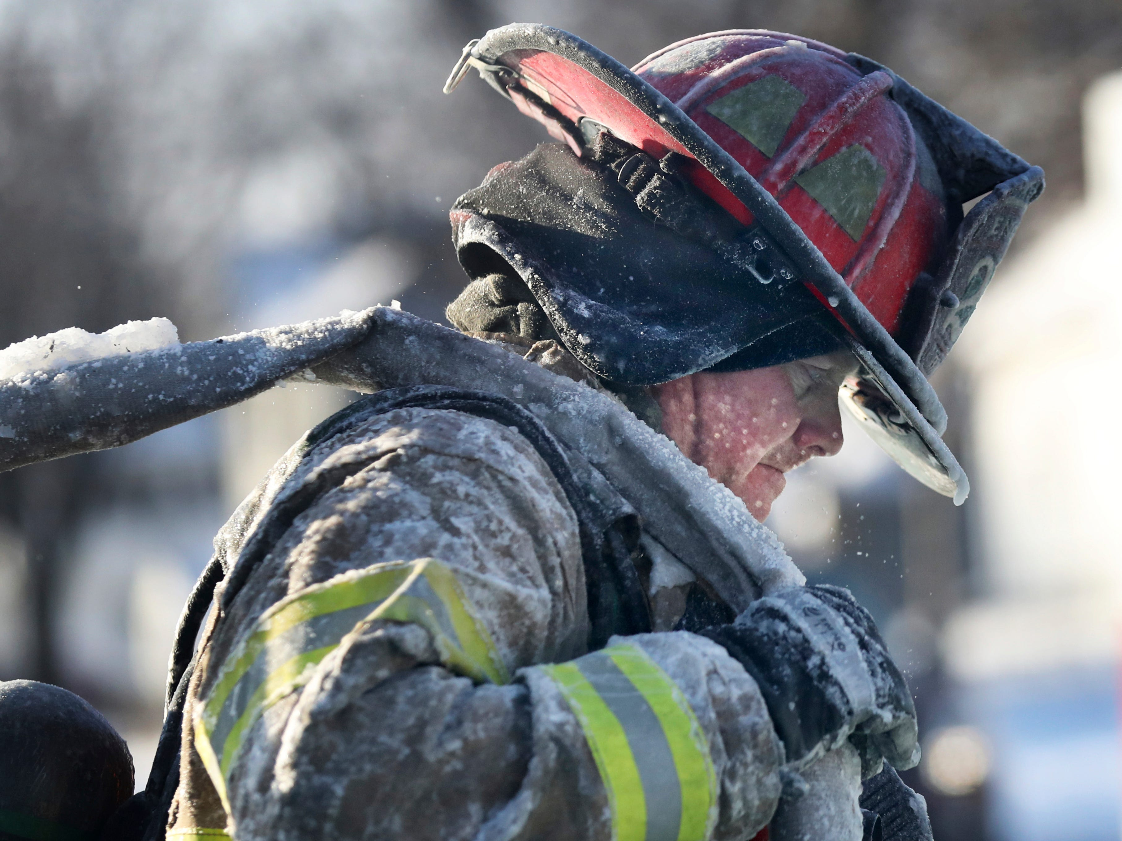 A St. Paul firefighter works at the scene of a house fire during a arctic deep freeze, Jan. 30, 2019, In St. Paul, Minn.