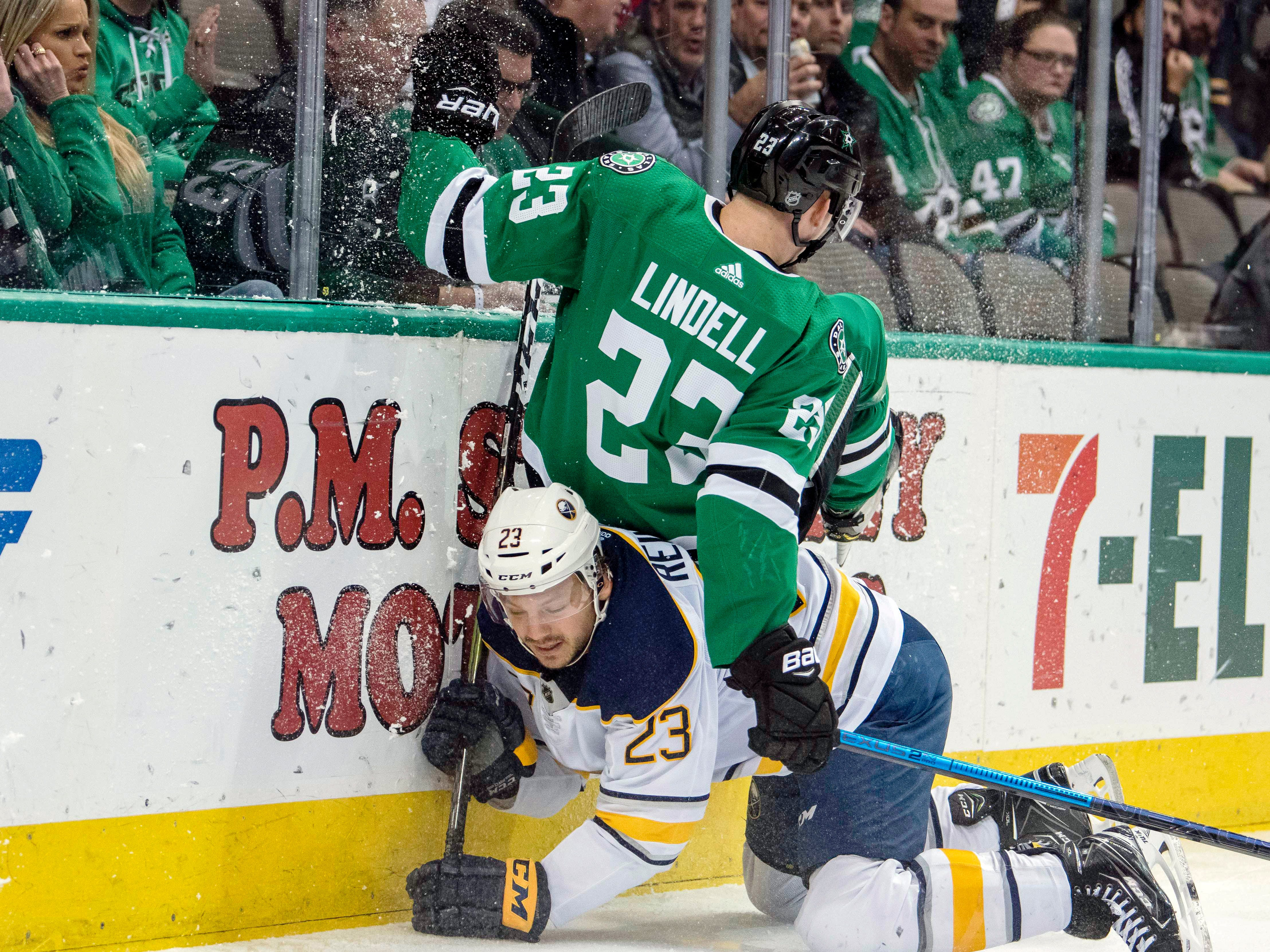 Jan. 30: Dallas Stars defenseman Esa Lindell and Buffalo Sabres center Sam Reinhart (23) crash into the boards during the first period at the American Airlines Center. The Stars won the game, 1-0.