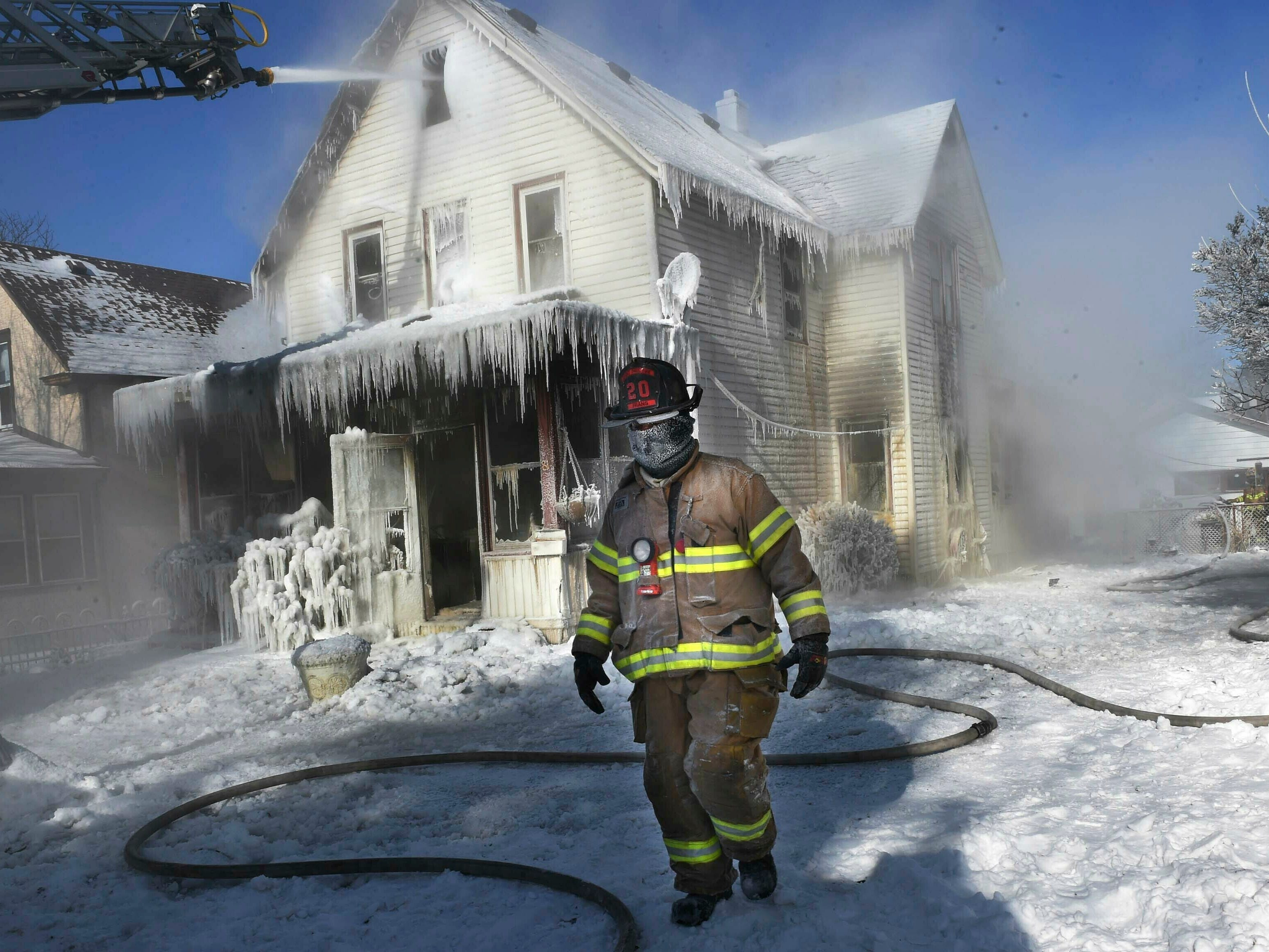A firefighter walks past an ice-encrusted home after an early morning house fire Jan. 30, 2019 in St. Paul, Minn. Firefighters were called to the house fire in the North End shortly after 4:15 a.m. The air temperature was 27 degrees below zero with wind chills at 52 degrees below zero. No injuries were reported.