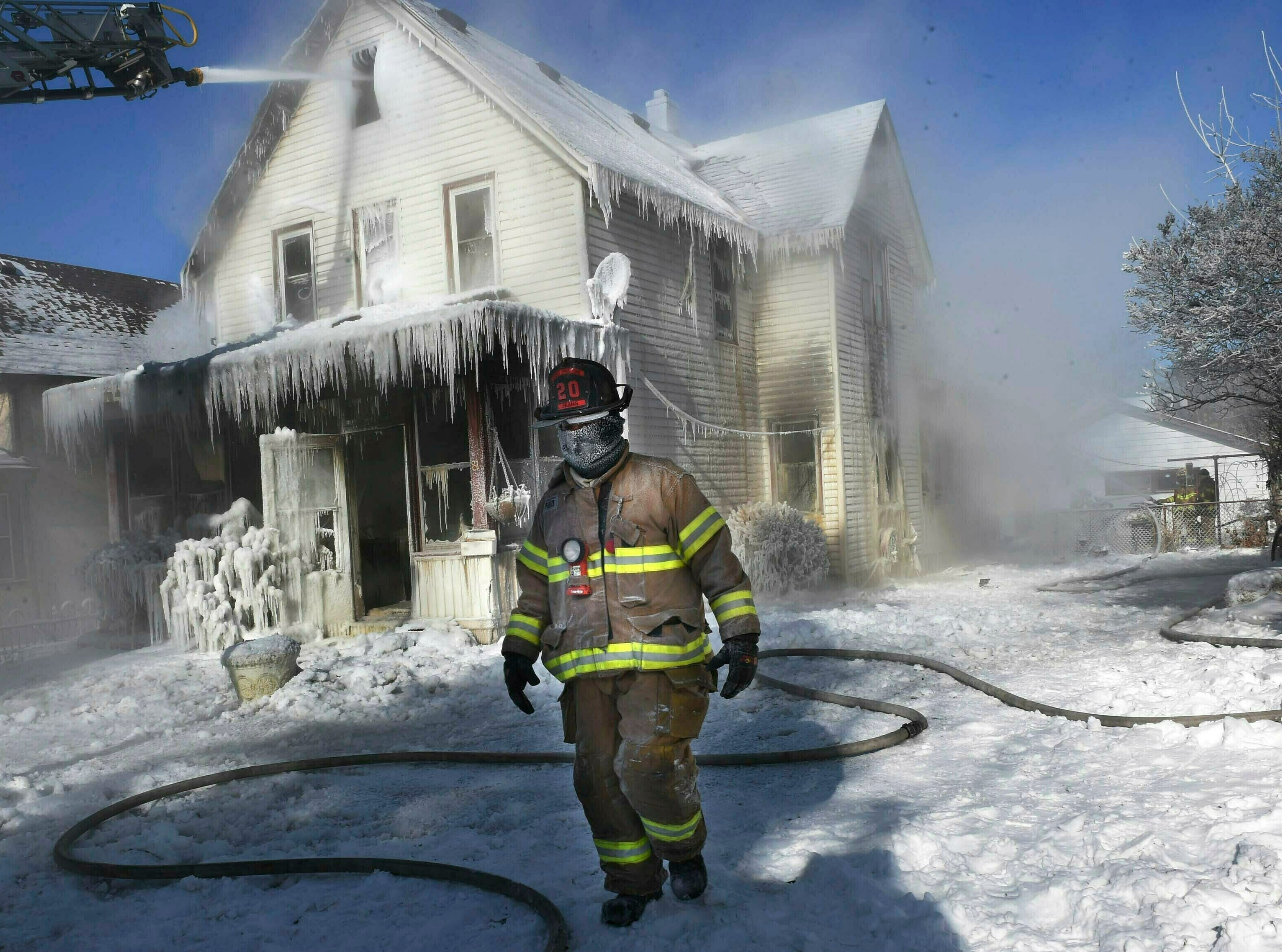 A firefighter walks past an ice-encrusted home after an early morning house fire Wednesday, Jan. 30, 2019 in St. Paul, Minn. Firefighters were called to the house fire in the North End shortly after 4:15 a.m. The air temperature was 27 degrees below zero Wednesday morning, with windchills at 52 degrees below zero. No injuries were reported.