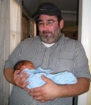 Lee Stern holds a friend's newborn in Los Angeles in 2007.