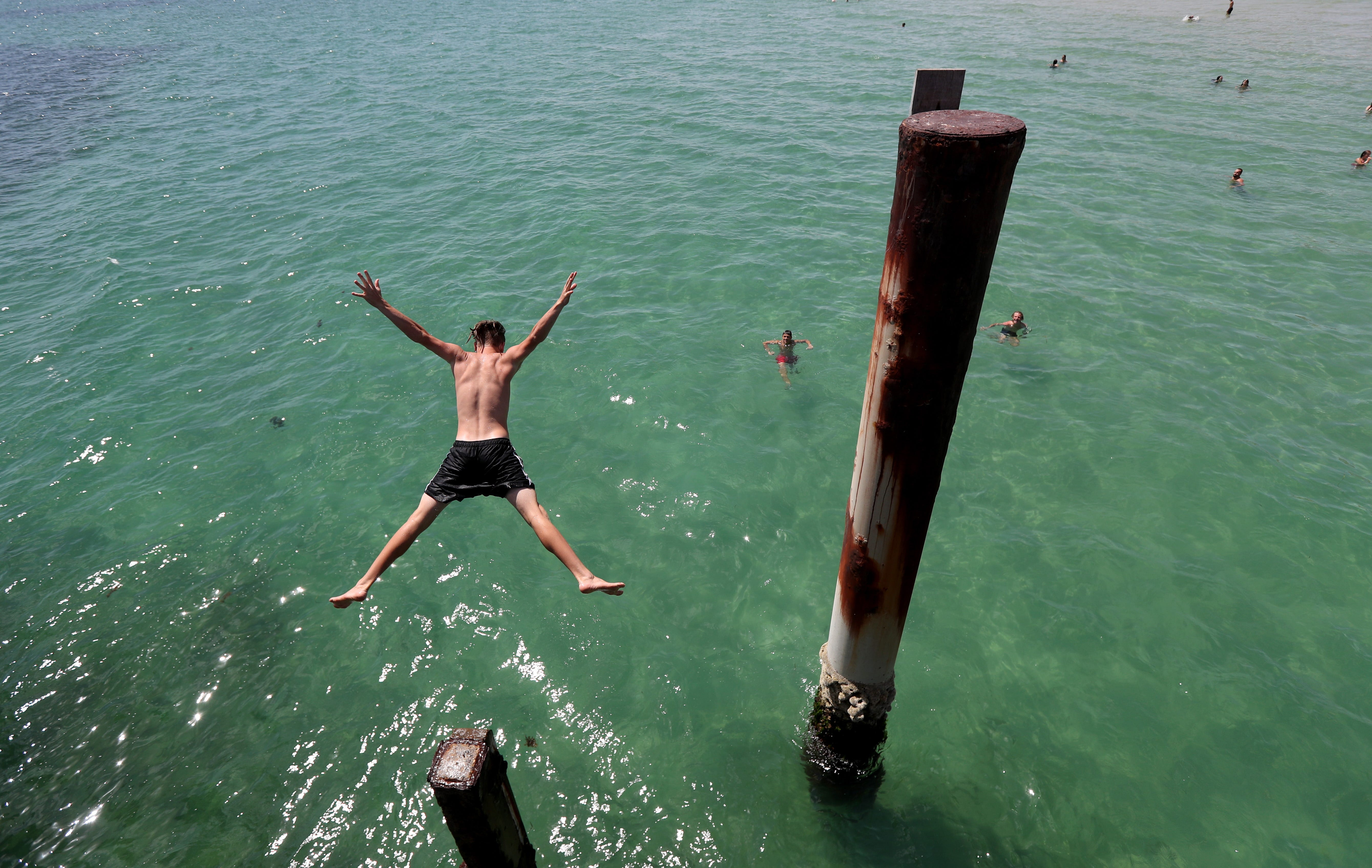 Teens jump of the jetty at Glenelg beach during a hot day in Adelaide, South Australia, Australia on Jan. 22, 2019. According to weather forecast, hot and dry weather will affect South Australia with winds reaching 30-40 kph during the daytime.