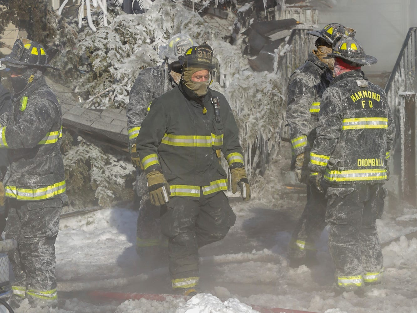 A Hammond, Indiana fire fighter is covered with ice at a fire in Hammond, Ind., Jan. 30, 2019. Fire fighters were hampered by the brutally cold sub-zero temperatures.