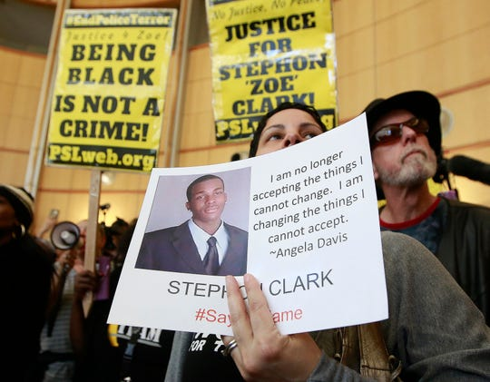 In this March 22, 2018, file photo, Anita Ross holds a photo of shooting victim Stephon Clark as she and other protesters block the entrance to Sacramento City Hall.