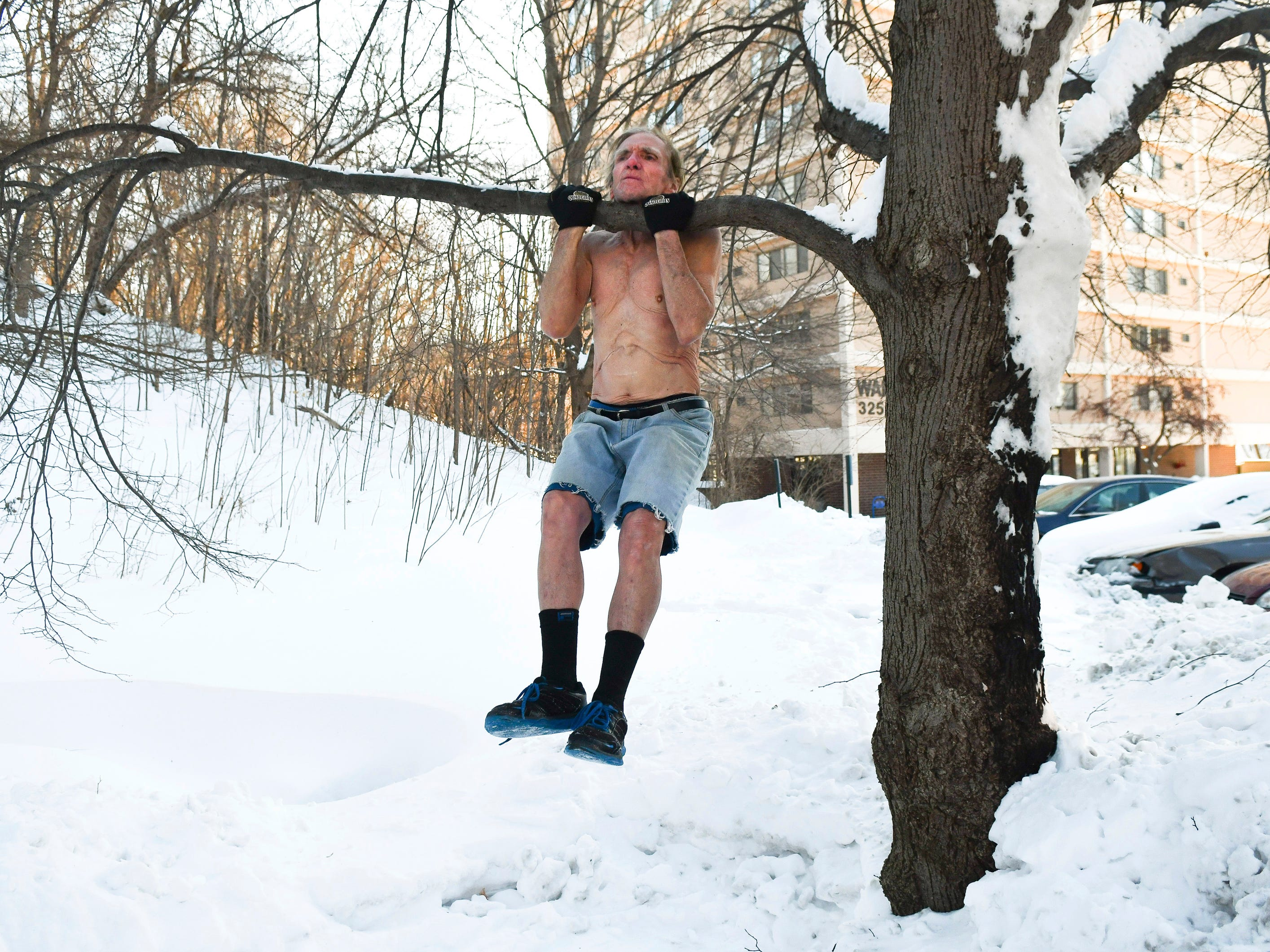 "John C. Anderson, 74, braves a minus 27 windchill to do shirtless pull-ups on a tree branch outside, in Silvis, Ill.. Jan. 30, 2019. ""It's going to be a historically cold day and I wanted to do something nobody else dare do,"" said Anderson, who is known for his fitness stunts. ""A lot of people think all old people are cold, they got cold blood...I wanted to show them not all old people are that cold blooded, certainly I'm not,"" said Anderson."