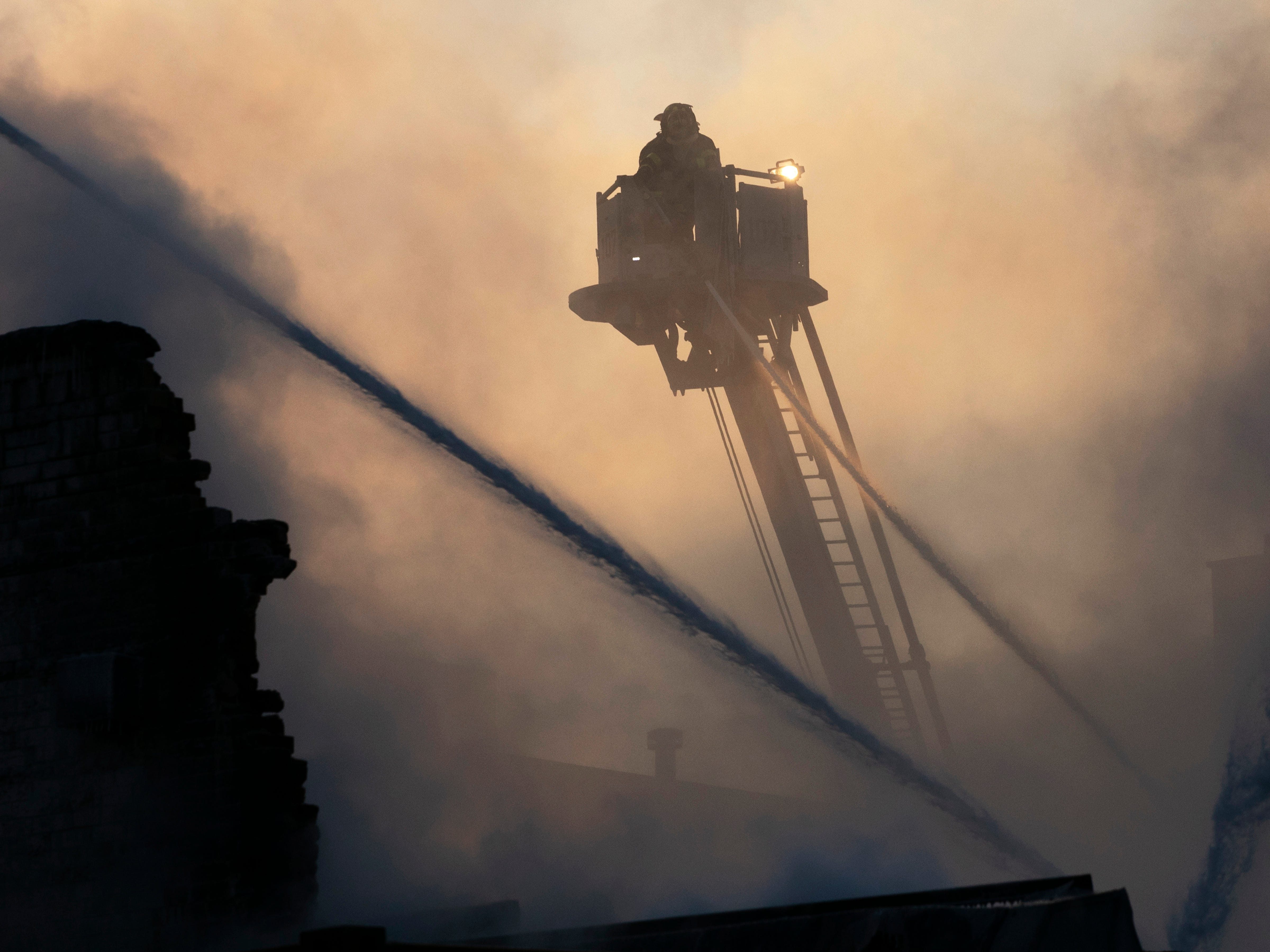 New York firefighters battle a blaze in a commercial building in the Bedford Stuyvesant neighborhood of Brooklyn, Jan. 31, 2019 in New York. Firefighters around New York state have been grappling with brutal cold during big blazes.