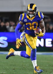 Los Angeles Rams running back Todd Gurley (30) runs against the Dallas Cowboys in the third quarter in a NFC Divisional playoff football game at Los Angeles Memorial Coliseum.