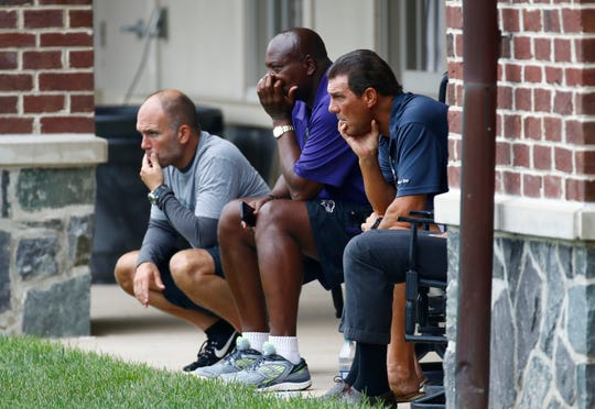 Baltimore Ravens general manager Eric DeCosta, far left, former general manager Ozzie Newsome and owner Stephen Bisciotti look on during a 2017 practice.