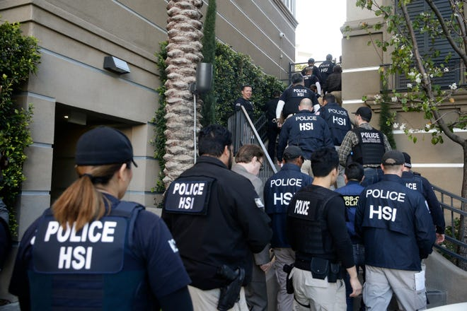 In this 2015 file photo, federal agents enter an upscale apartment complex where authorities say a birth tourism business charged pregnant women $50,000 for lodging, food and transportation, in Irvine, Calif. On  Jan. 31, 2019, authorities announced they have charged 20 people in an unprecedented crackdown on the businesses.