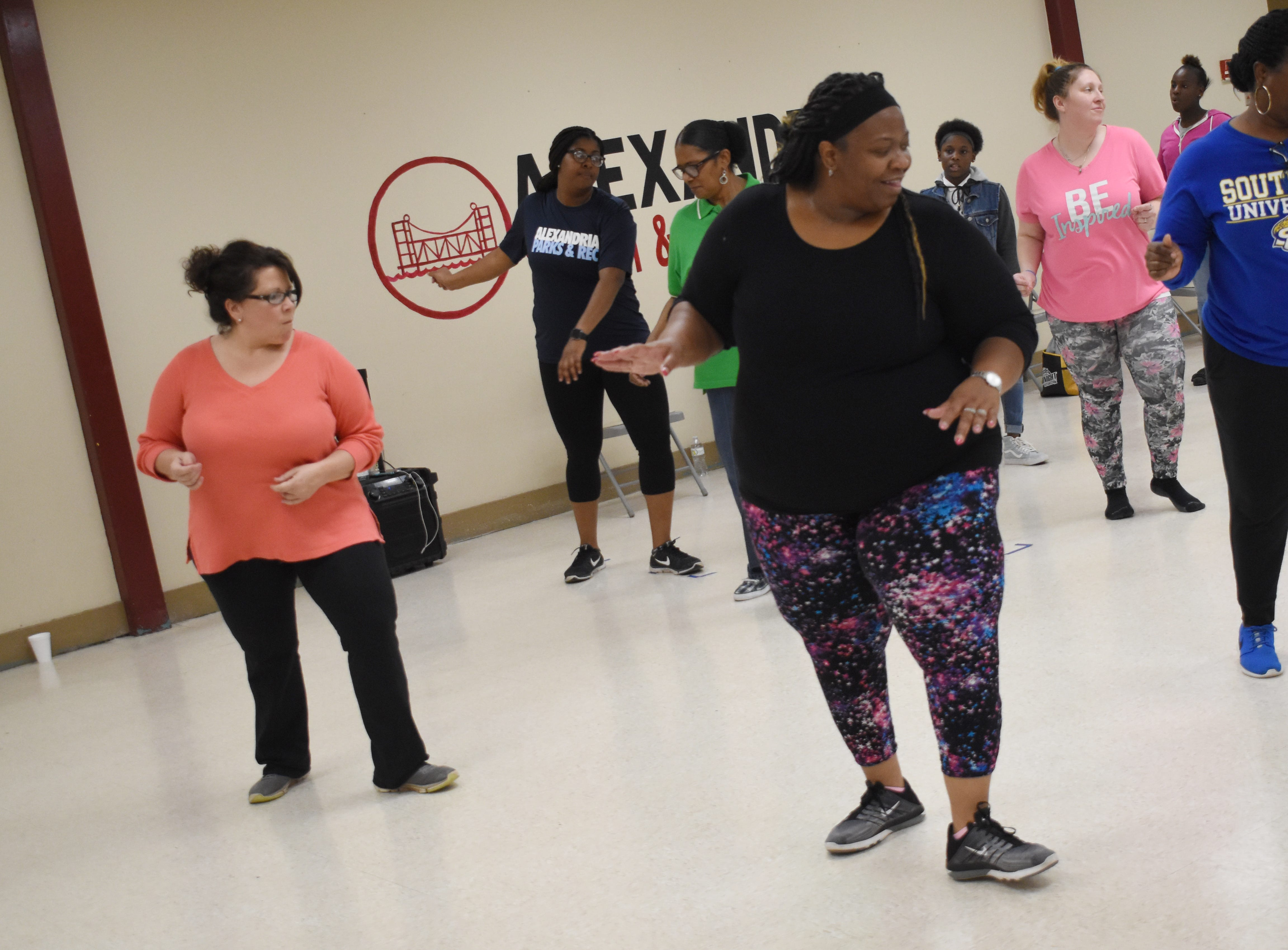"Anna Brodhead (back left) and Benita Gaston (front right) learn steps to a line dance from Sakena Cannon (back center) at the Alexandria Youth & Teen Center. Sakena, along with her sister Aketa Cannon, are instructing free line dancing classes at 6 p.m. every Tuesday and Thursday at the Alexandria Youth & Teen Center located in the former Boys and Girls Club on Sylvester Street. Some of the line dances Sakena and Aketa have taught so far include the ""Cleveland Shuffle,"" ""Same Ole 2 Step,"" ""Do It With Your Boots"" and the ""Mississippi Shuffle."