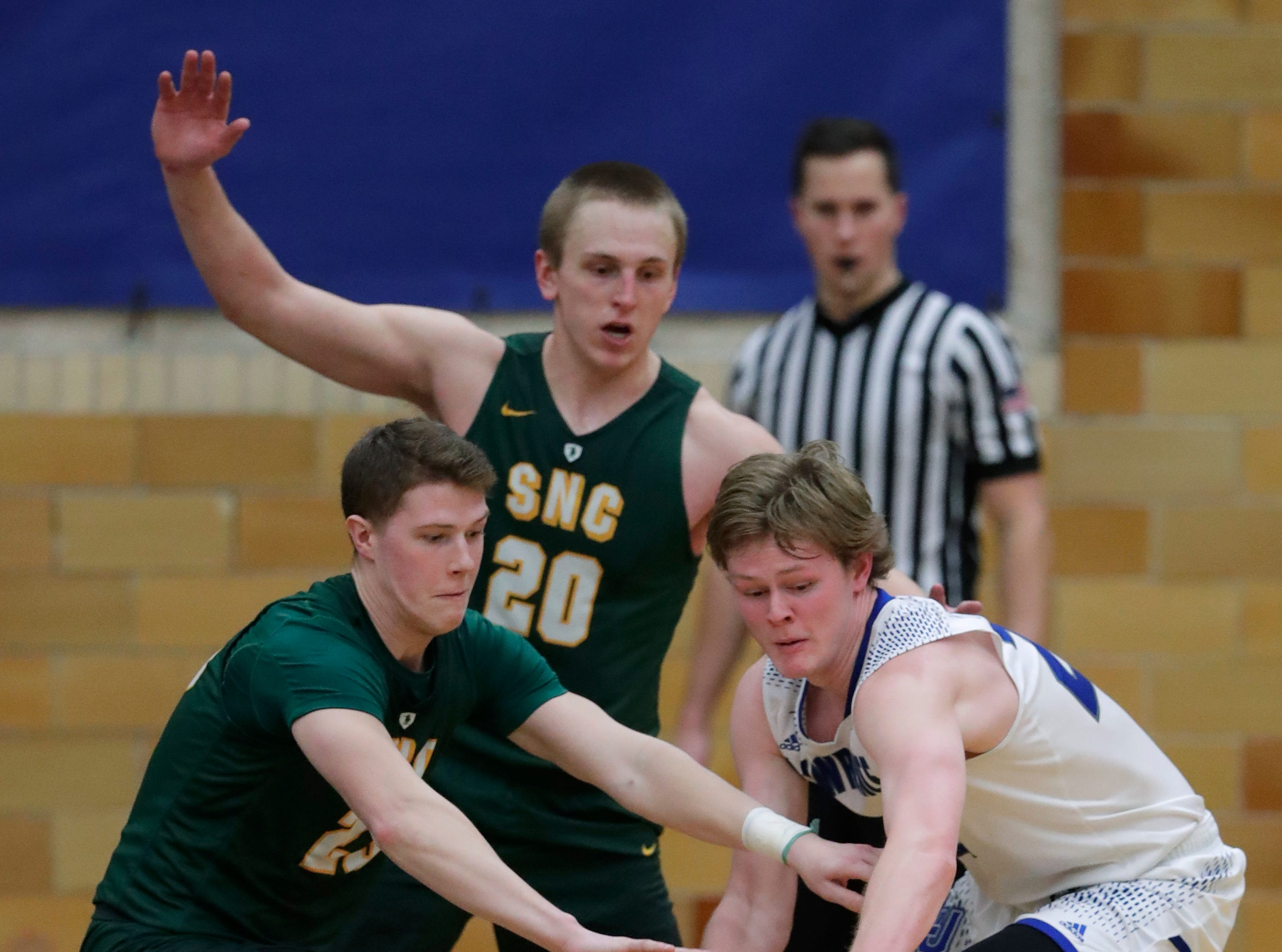 Lawrence University's Mason Maerna (22) tries to gain control of the ball against St. Norbert College's Drew Yetka (23) and Nolan Beirne (20) during their men's basketball game Thursday, January 31, 2019, at Alexander Gymnasium in Appleton, Wis. 
