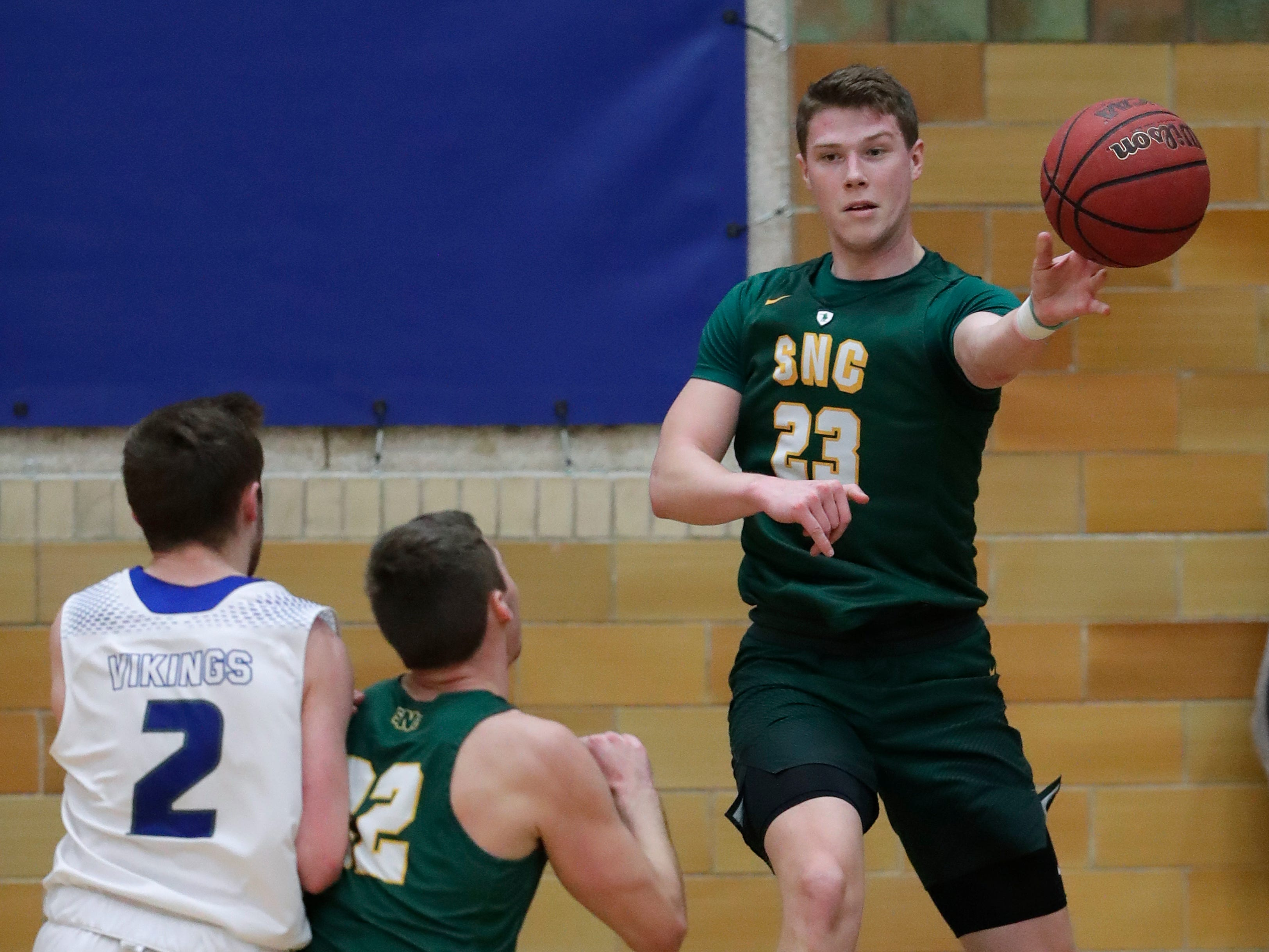 St. Norbert College's Drew Yetka (23) saves the ball from going out of bounds as he passes the ball to Wade Geenen (22) as Lawrence University's Quinn Fisher (2) defends during their men's basketball game Thursday, January 31, 2019, at Alexander Gymnasium in Appleton, Wis. 