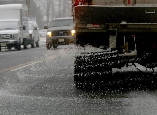 An Ocean County road department truck spreads salt along Brown Avenue in Lakehurst
