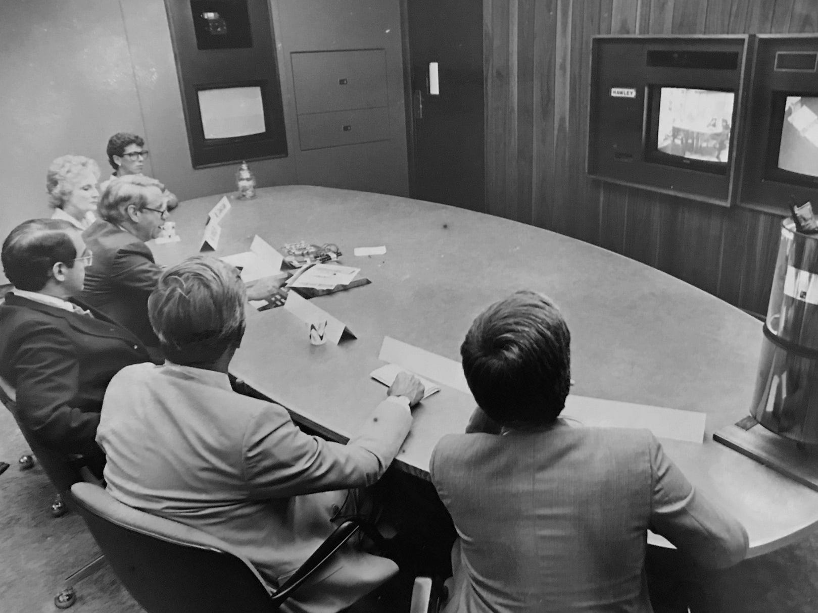 August 16, 1985 David G Thomas (wearing dark jacket and glasses), executive director of AT&T Transmission Systems Division leads a demonstration of video teleconferences via satellite yesterday at Bell Laboratories in Holmdel Township while he views and talks to other particip[ants who are in Hawley PA.