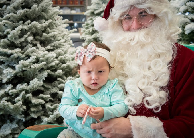 Rosalia is skeptical of Santa (Staff Sgt. Michael Pace, of the Dyess We Care Team).