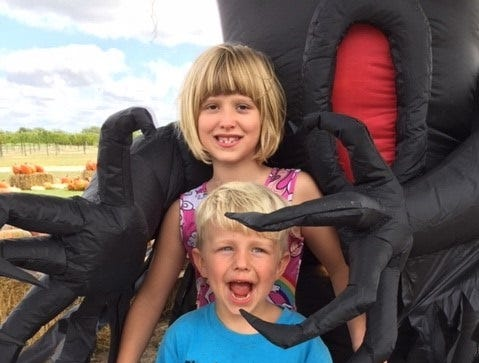 Jocelyn Bibby and Benjamin Manley, great-grandchildren of Doug and Johanna May, of Clyde, enjoy some Halloween fun at the Denton Valley Farm Store.