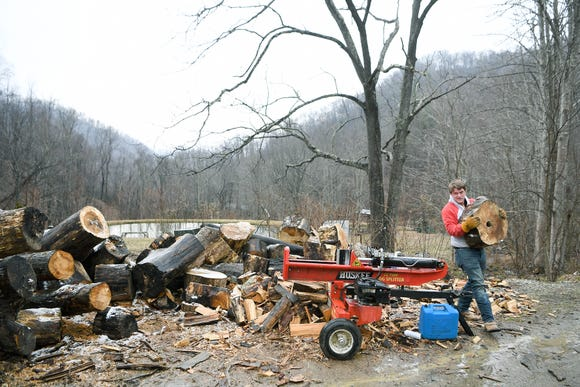 Colton Roberts carries a log to his log splitter to make firewood at his home in Madison County on Jan. 17, 2019. The entrepreneurial high school senior spends his evenings and weekends chopping and delivering firewood to customers to earn money.