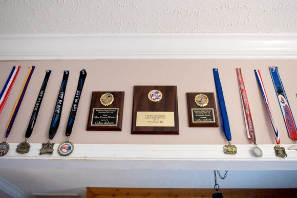 Medals and plaque line the wall above a doorway in Colton Roberts' Madison County home. The Madison High School senior is a wrestler and baseball player.