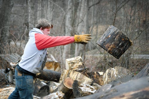 Colton Roberts tosses a log as he makes firewood at his home in Madison County on Jan. 17, 2019. The entrepreneurial high school senior spends his evenings and weekends chopping and delivering firewood to customers to earn money.