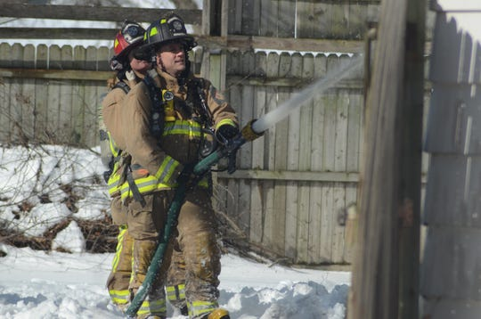 Battle Creek Firefighters fight the fire on Cedar Street from the back of the house.
