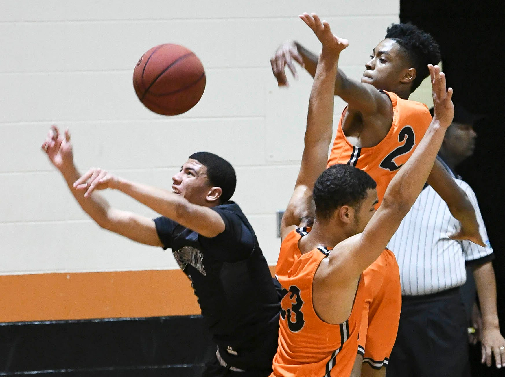 Tony Wright of Melbourne battles for a rebound with Kendal Parker and Joseph Cartwright of Cocoa during Thursday's game.