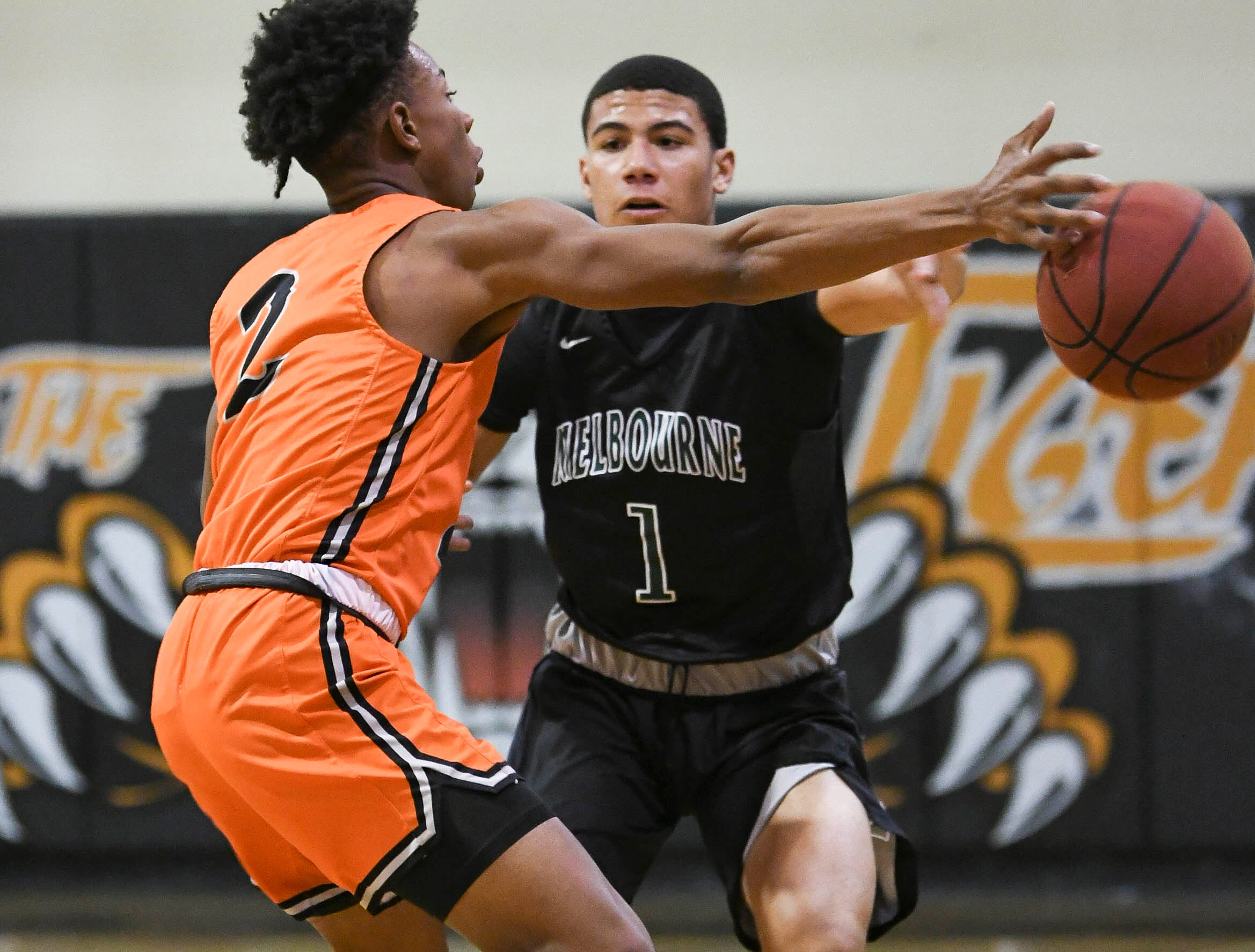 Melbourne's Tony Wright (1) passes around the guard of Cocoa's Jay Robinson Thursday at Cocoa High School.