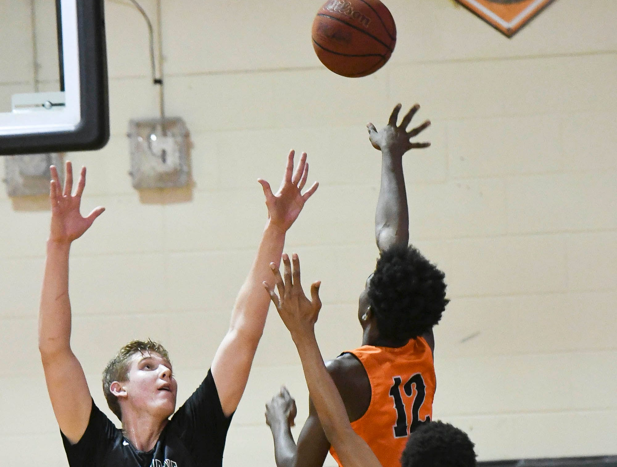 Cocoa's Jimmy Bell (12) shoots over Melbourne's Max Fiedler during Thursday at Cocoa High School.'s game.