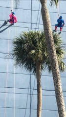 Suzy Fleming Leonard, left, and Scott Earick rappel down the side of Melbourne Rialto Hilton during Over the Edge, a fundraiser for Habitat for Humanity of Brevard.