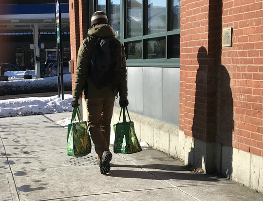 A City Market shopper totes two re-usable shopping bags in Burlington on Friday, Feb. 2, 2019.