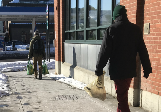A City Market shopper toting two re-usable shopping bags in Burlington walks in front of man who opted for a plastic bag on Friday, Feb. 2, 2019.