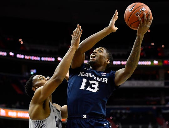Xavier Musketeers forward Naji Marshall (13) shoots as Georgetown Hoyas guard Kaleb Johnson (32) defends during the first half at Capital One Arena.