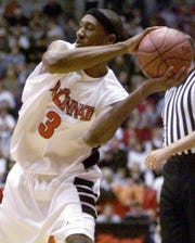 Text: FILE--Cincinnati freshman guard DerMarr Johnson looks to pass the ball during a preseason game with B.C. Honved of Hungary, in this Saturday, Nov. 6, 1999 file photo taken in Cincinnati. Johnson is the most highly rated freshman at Cincinnati since Danny Fortson. The Bearcats are ranked number one in this week's Associated Press poll. (AP Photo/Al Behrman, File)