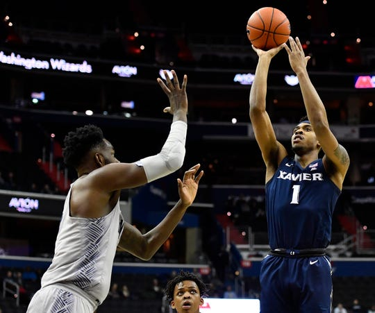 Xavier Musketeers guard Paul Scruggs (1) shoots as Georgetown Hoyas center Jessie Govan (left) looks on during the first half at Capital One Arena.