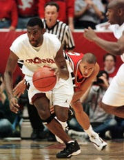 Text: Cincinnati forward Pete Mickeal, left, heads upcourt after stealing the ball from Louisville guard Cameron Murray, rear, in the first half, Sunday, Feb. 21, 1999, in Cincinnati. Cincinnati guard Michael Horton is at right. Mickeal scored 28 points to lead Cincinnati to a 91-78 win. (AP Photo/Al Behrman)