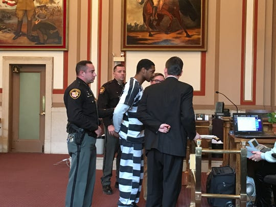 Recardo Woods, at center, talking to his attorneys in Hamilton County Common Pleas Court Friday, Feb. 1, 2019.
