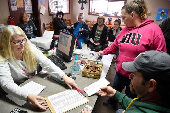 Sherry Travers helps Tommi Jo French and Eddie Goering as they fill out paperwork to pick up food at the Manna Cafe Monday, Jan. 28, 2019, in Clarksville, Tenn. They have been living on the streets but just recently acquired an apartment.