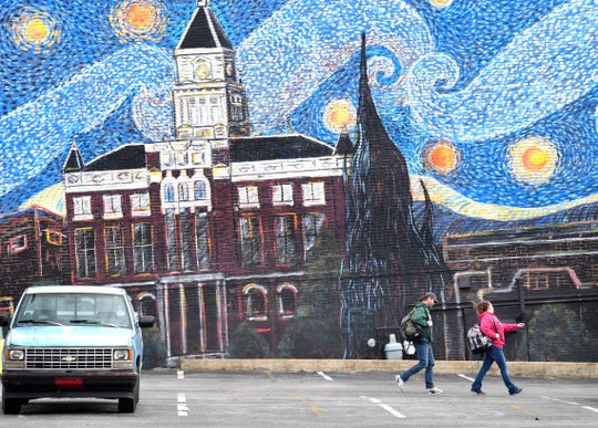 Tommi Jo French and Eddie Goering walk past a mural on Jan. 28 in Clarksville, near where they pitched a tent in a vacant lot because they were homeless. They recently acquired an apartment through Operation Stand Down.
