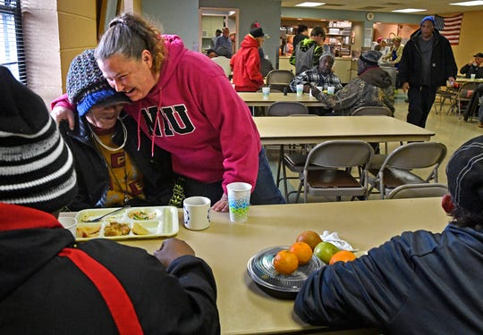 Tommi Jo French gives a hug as she talks with Charles Gaines at the Loaves and Fishes food ministry where she has received many meals while being homeless.