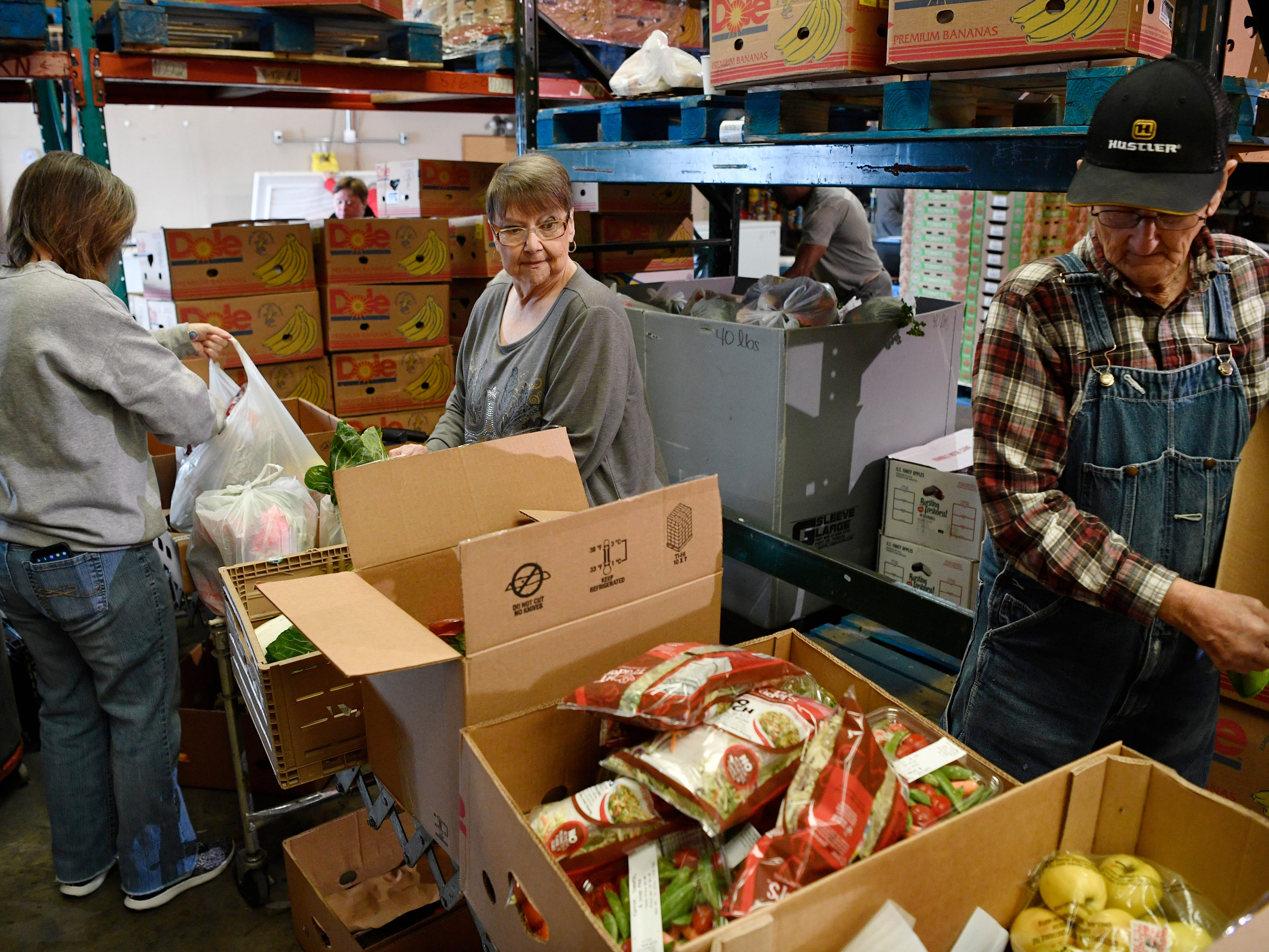Mary Goodwin, Dawn Spicer and Kent Paschal sort fresh produce that will be given out to those in need at the Manna Cafe Monday, Jan. 28, 2019, in Clarksville, Tenn.