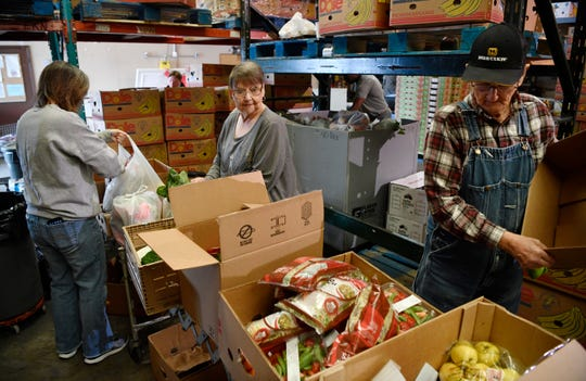 Mary Goodwin, Dawn Spicer and Kent Paschal sort fresh produce that will be given out to those in need at Manna Cafe on Jan. 28, 2019, in Clarksville, Tenn.