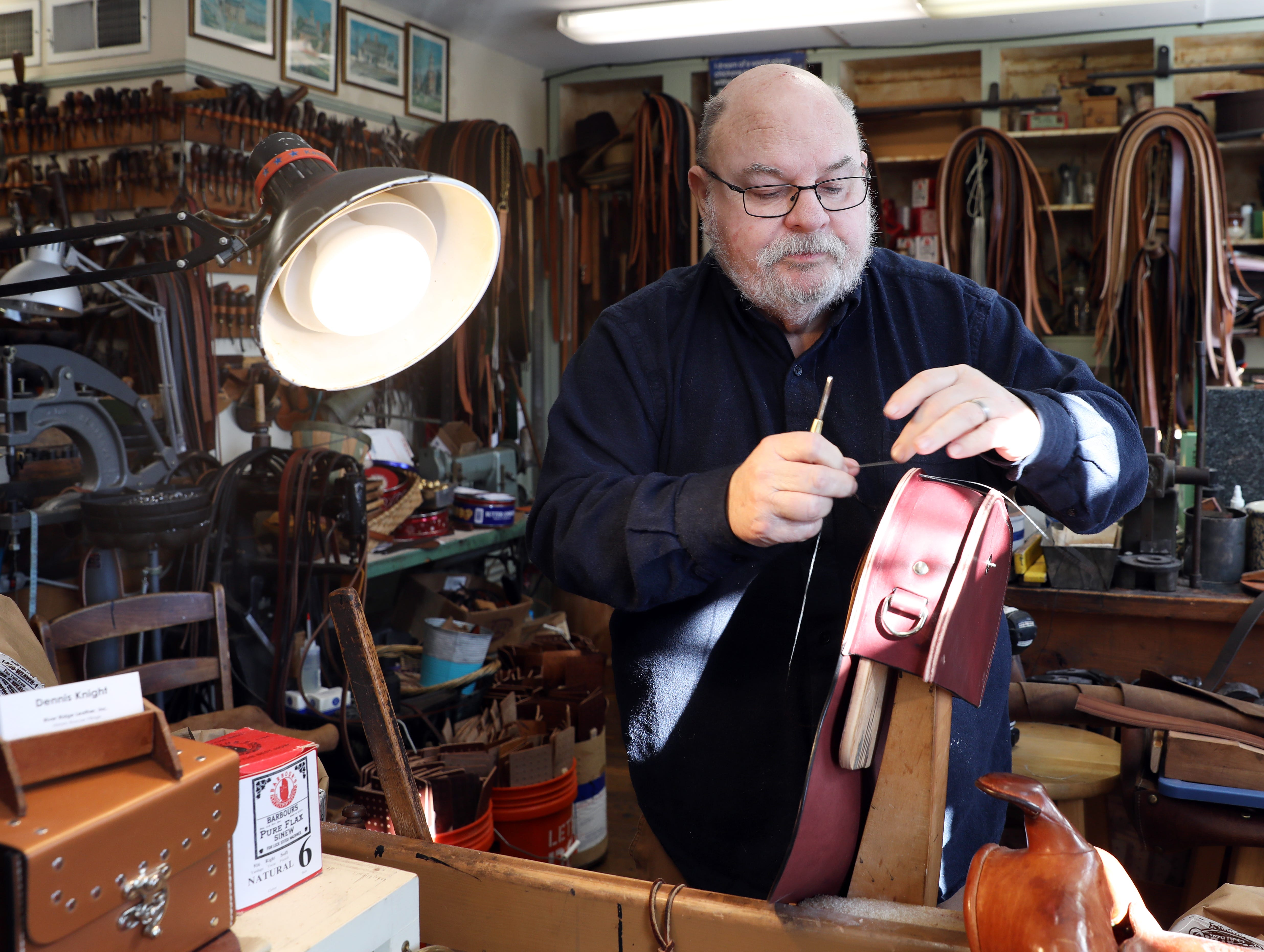 Dennis Knight, owner of River Ridge Leather Company in Roscoe Village, works on a bag in his shop.