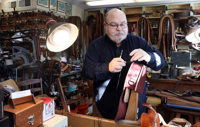 Dennis Knight, owner of River Ridge Leather Company, works on a bag in his shop. River Ridge Leather is one of many shops in Roscoe Village.