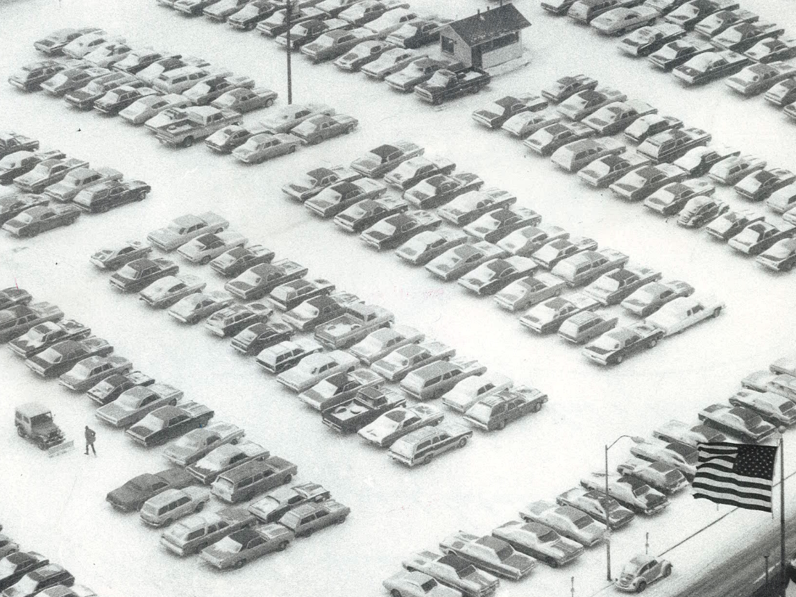 From 1975: A November 1975 snowstorm decorated rows of cars parked in a lot at Ninth and Pleasant streets in Des Moines. A lone attendant, lower left, works to clear the lot.