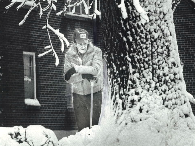 From 1983: Gene Looker, 57, leans on his shovel after clearing snow from in front of his home at the Hampton House Apartments at 42nd and Grand in Des Moines.